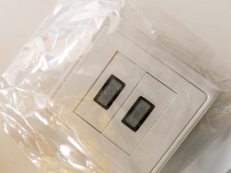 Interruptor de iluminação eclético branco em um saco de plástico transparente preparado para a instalação fotografia de stock royalty free