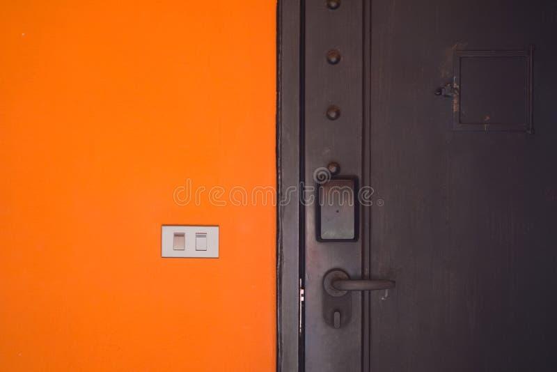 Interruptor de la electricidad en la pared anaranjada del cemento foto de archivo