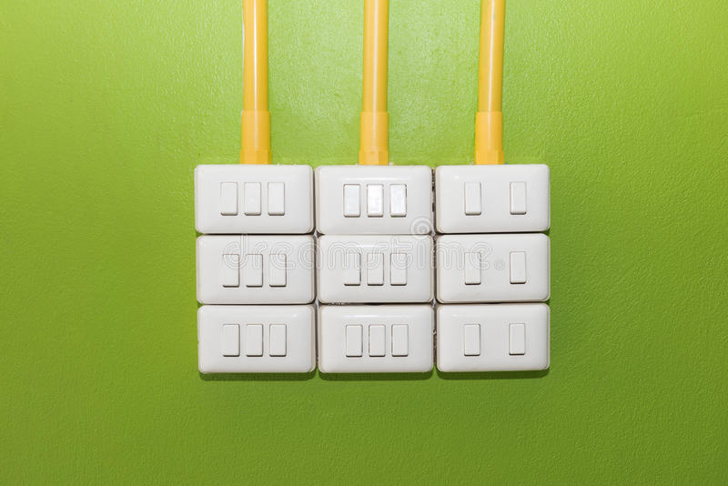 Interruptor de la luz blanco eléctrico del eje de balancín en la pared verde imagen de archivo libre de regalías