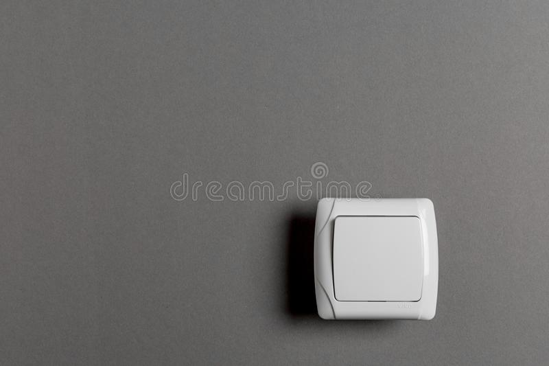 Interruptor de la luz en una pared gris foto de archivo