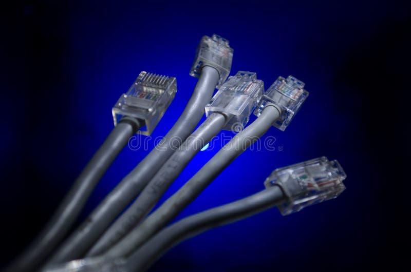Interruptor de rede e cabos ethernet, símbolo de comunicações globais A rede colorida cabografa no fundo escuro com luzes e smo imagem de stock royalty free