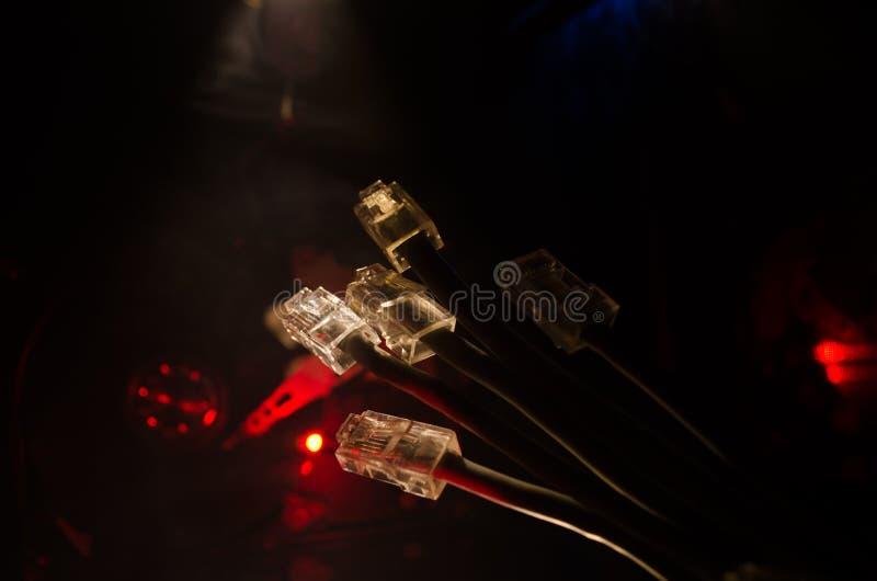 Interruptor de rede e cabos ethernet, símbolo de comunicações globais A rede colorida cabografa no fundo escuro com luzes e smo imagens de stock royalty free