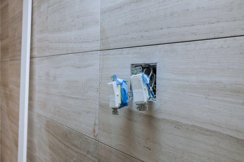 Interruptor eléctrico de la instalación blanca con los alambres de conexión en la pared ligera interior del cuarto de baño fotos de archivo