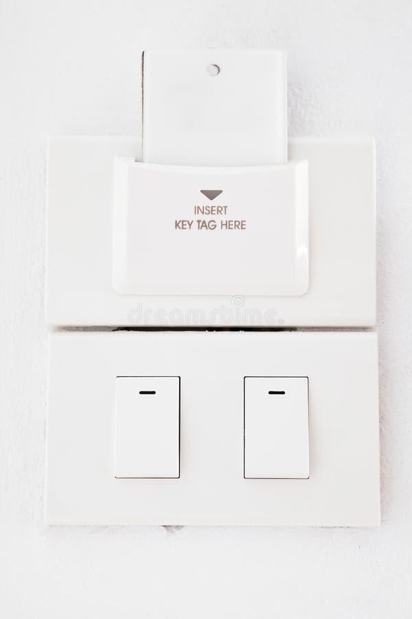 Interruptor leve e Tag chave em branco na parede fotos de stock