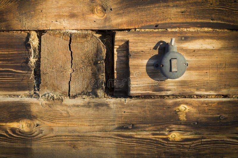 Interruptor plástico preto em uma parede de madeira velha imagem de stock