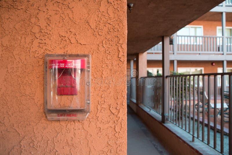 Interruptor vermelho do alarme de incêndio na parede do cimento imagem de stock