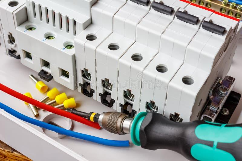 Interruptores automáticos instalados no trilho do RUÍDO na caixa de montagem plástica branca em um fundo dos fios e da chave de f fotos de stock royalty free