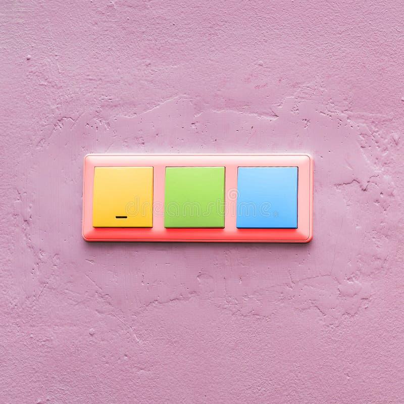 interruptores da luz Multi-coloridos em uma parede cor-de-rosa Interruptor elétrico colorido elegante Estilo creativo Arte do con imagens de stock