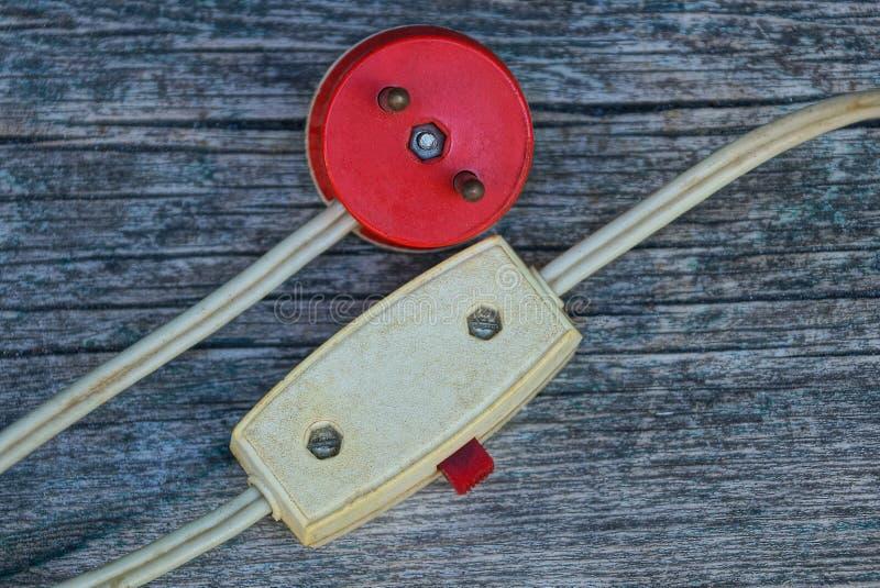 Interruttore basculante rosso della plastica e della spina elettrica su un cavo su un bordo di legno grigio fotografie stock