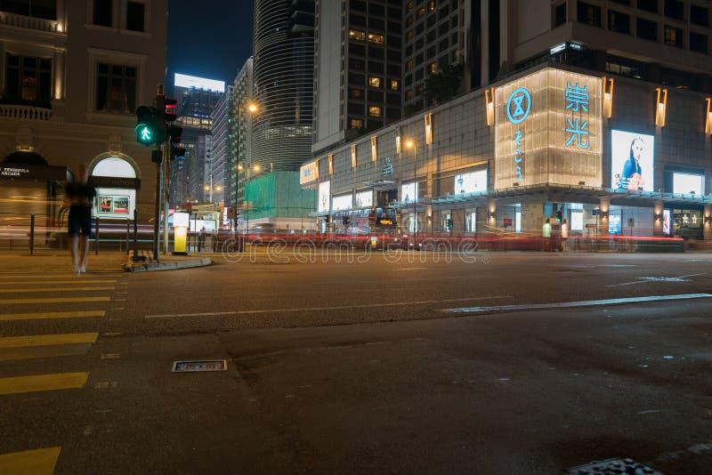 A interseção famosa da cidade na noite iluminou a construção, as lojas e a rua do cruzamento da pessoa imagem de stock