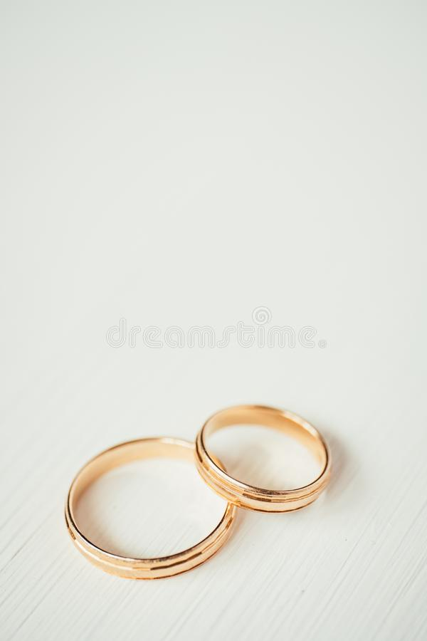 Intersecting wedding gold rings at the bottom of the white wooden background. Vertical royalty free stock images