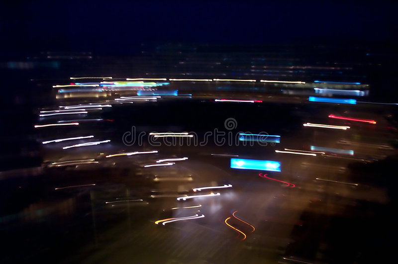 Intersection at night. A roundabout intersection at night, the camera as shaken to achieve a blurry effect stock images