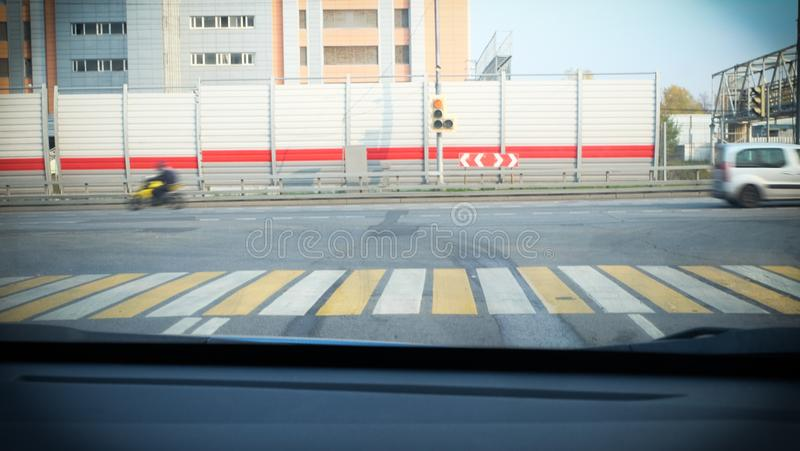 At the intersection of t-shaped cars are at a traffic light and wait for the green signal and on the road passing motorcycle royalty free stock photo