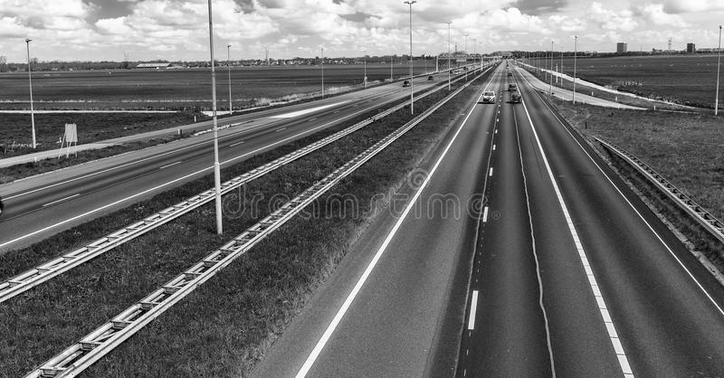 Interstate road in open countryside with blue car speeding up royalty free stock photos