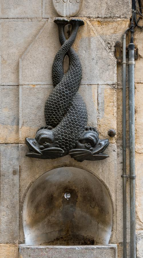 Intertwined fish sculpture on the wall on top of the drinking fountain in Girona, Spain. Sculpture of intertwined fish on the wall on top of the drinking stock image