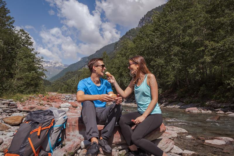 Intervallo di pranzo delle coppie di viaggiatori con zaino e sacco a pelo con landjaeger e pane su un fiume immagini stock libere da diritti