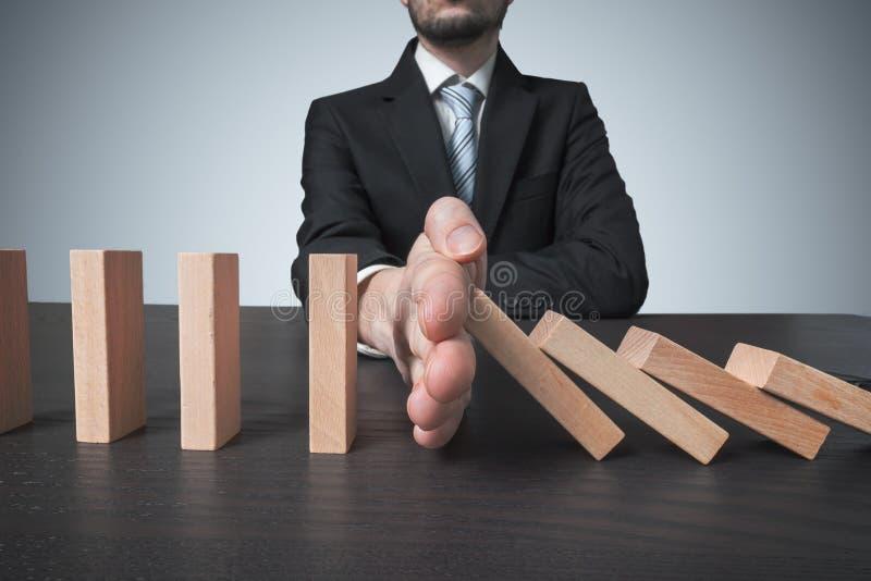 Interventieconcept De mens houdt dalende domino met hand tegen stock afbeelding