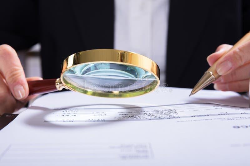 Interventor Inspecting Financial Documents en el escritorio imagen de archivo