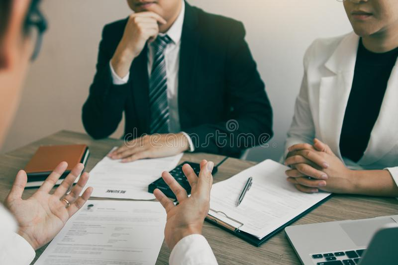The interview room while the staff is preparing the resume document and presenting to the manager who is talking and analyzing. About the work experience stock photo