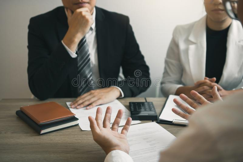 The interview room while the staff is preparing the resume document and presenting to the manager who is talking and analyzing. About the work experience stock image