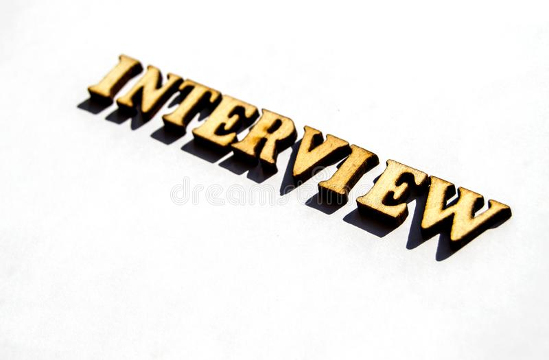 Interview-a word of wooden vintage letters to represent the meaning of the financial word as a concept on a white background with. Shadows from sunlight royalty free stock photography