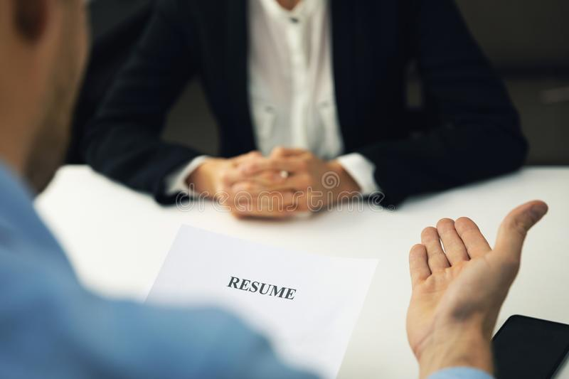 Interviewer and candidate discussion in a job interview reviewing resume stock photo