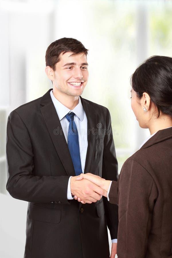 Interviewer, der Hand zum zukünftigen Angestellten rüttelt stockfoto