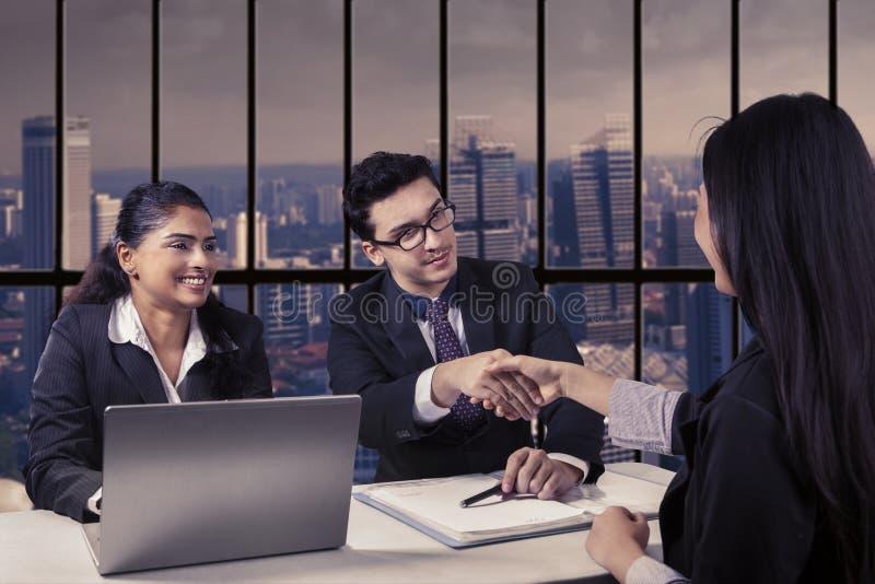 Interviewer het schudden handen met nieuwe werknemer stock foto's