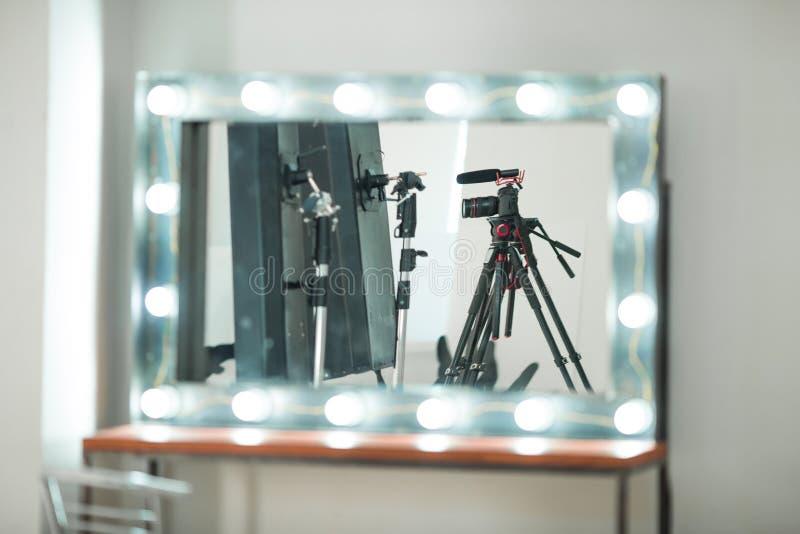 Intervista di concetto, macchina fotografica digitale su un treppiede con un microfono nello studio su un fondo bianco nella rifl fotografia stock libera da diritti