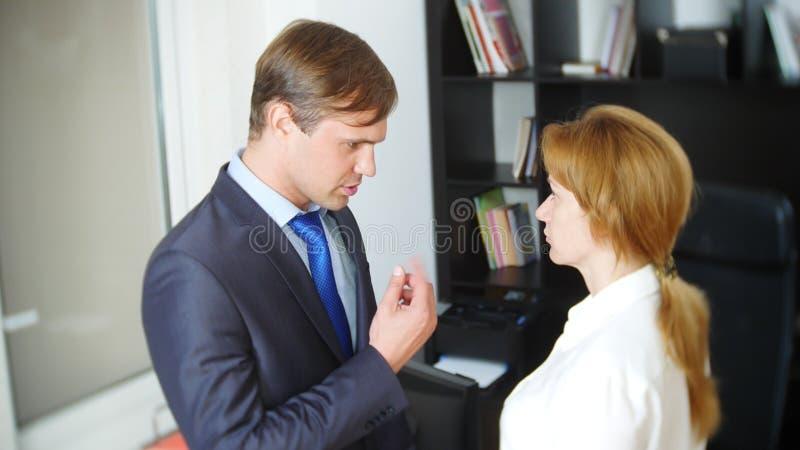Intervju med interlokutören eller ett möte: en affärsman och en kvinna blidka ironi fotografering för bildbyråer