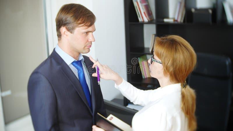 Intervju med interlokutören eller ett möte: en affärsman och en kvinna blidka ironi arkivbilder