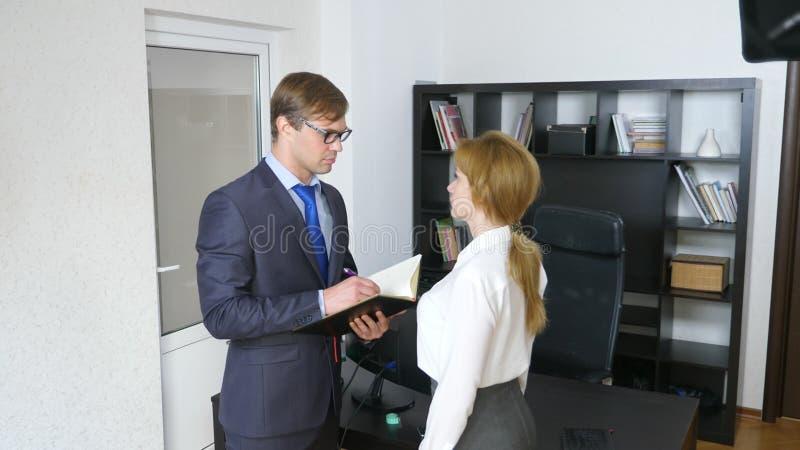 Intervju med interlokutören eller ett möte: en affärsman och en kvinna blidka ironi arkivfoton