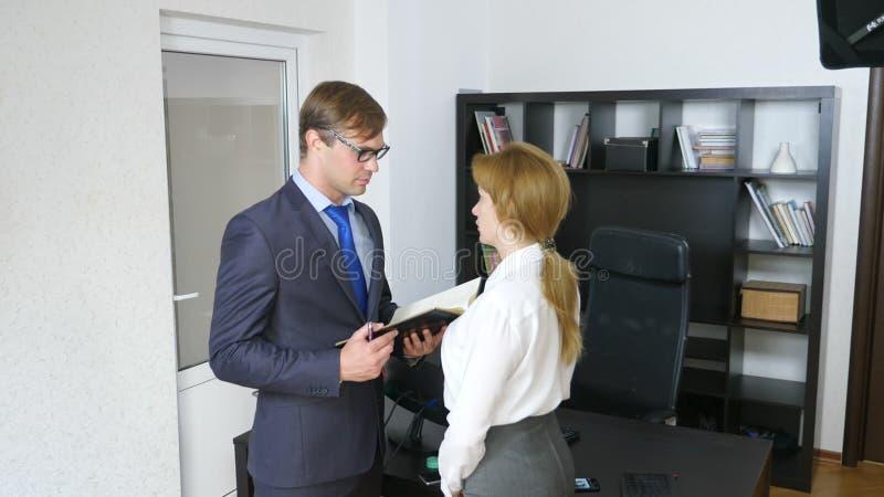Intervju med interlokutören eller ett möte: en affärsman och en kvinna blidka ironi royaltyfria bilder
