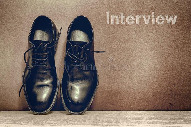Intervju p? bruna br?de- och arbetsskor p? tr?golv arkivbilder