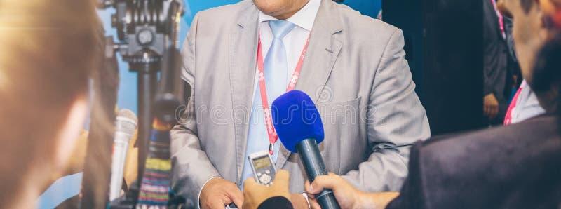 Intervjua affärsmannen på press på affärsmöte royaltyfria foton