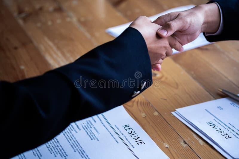 Intervjua f?r handskakningframg?ngjobb Jobbs?kande som har intervju Skaka handen med meritförteckningen på skrivbordet Arbetsgiva arkivfoton