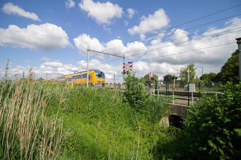 Intestazione del treno verso un passaggio a livello un giorno soleggiato fotografia stock
