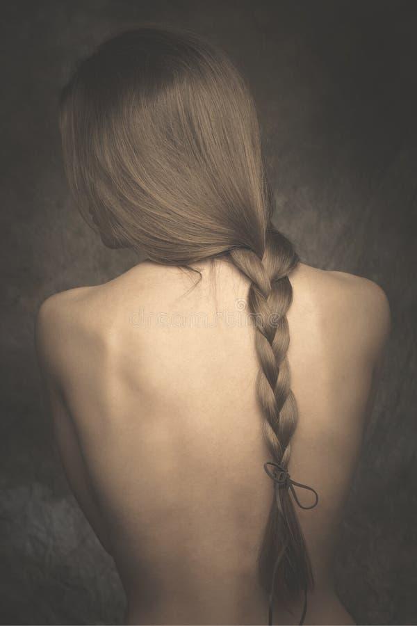Intim kal kvinnastående tillbaka och lång flätad tråd arkivfoto