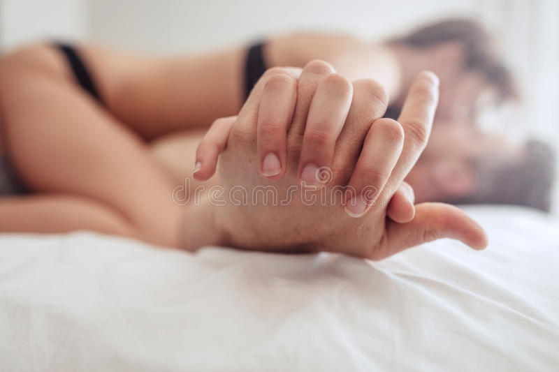 Intimate couple having sex on bed. Cropped image of intimate couple holding hands while having sex on bed