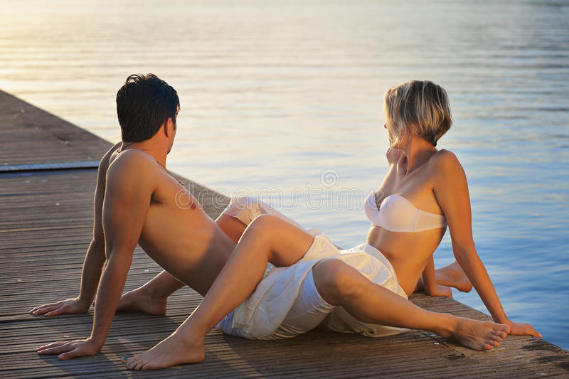 Intimate couple looking at sunset stock images
