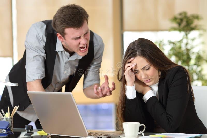 Intimidatie met een werkgever die aan een werknemer schreeuwen stock foto's
