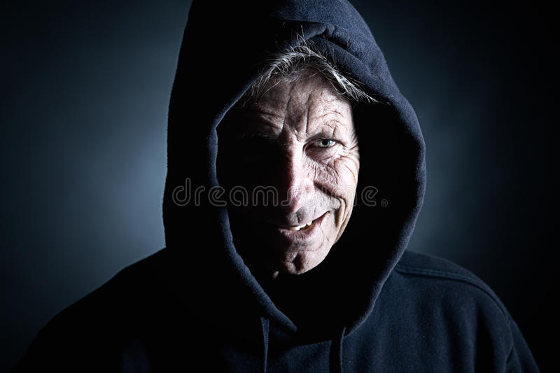 Intimidating Distinguished Man in Hooded Top. Low Key Shot of an Intimidating Distinguished Man in Hooded Top stock image