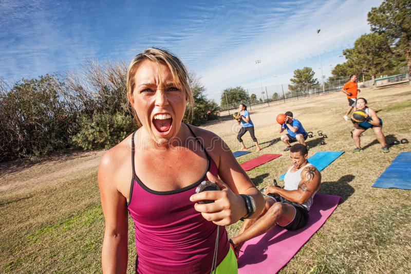 Intimidating Fitness Trainer. Intimidating boot camp fitness trainer with adult class outdoors royalty free stock images