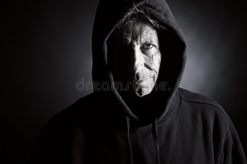 Intimidating Senior Male in Hooded Top. Low Key Shot of an Intimidating Senior Male in Hooded Top royalty free stock photos