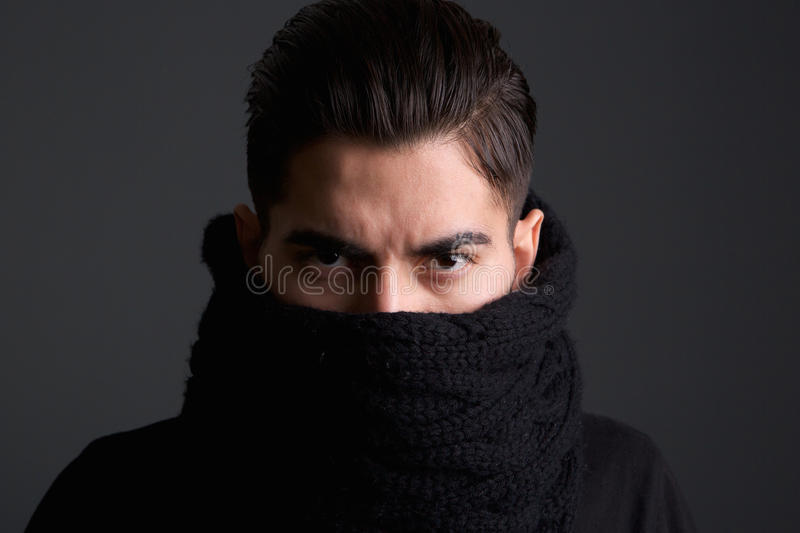 Intimidating young man with scarf covering face. Close up portrait of an intimidating young man with scarf covering face royalty free stock image