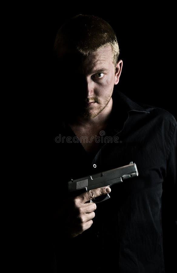 Intimiderend Mannetje dat een Kanon houdt aan zijn Borst stock foto's