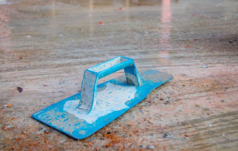Intonacatore blu sul lavoro Applicazione del gesso sulla parete del cemento Gesso strutturato immagini stock