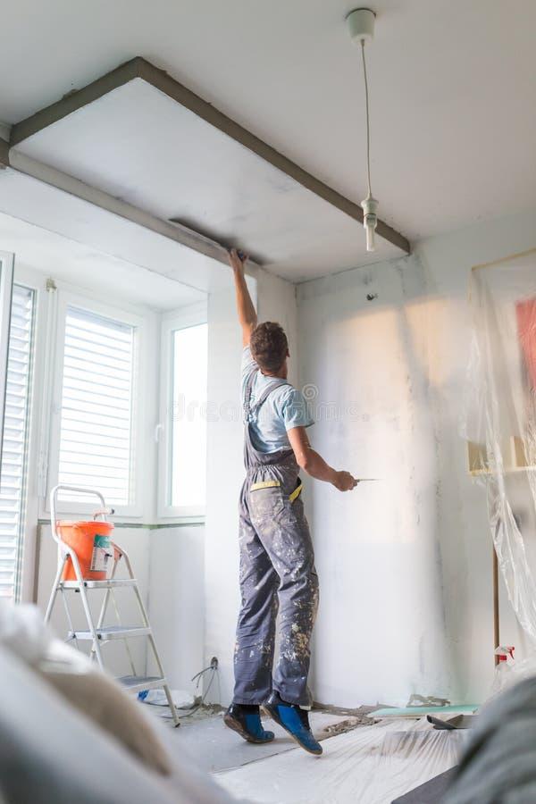 Intonacatore che rinnova le pareti ed i soffitti dell'interno Impianti di finitura fotografia stock