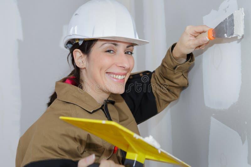 Intonacatore femminile che fa rinnovamento della parete con la spatola ed il gesso fotografia stock