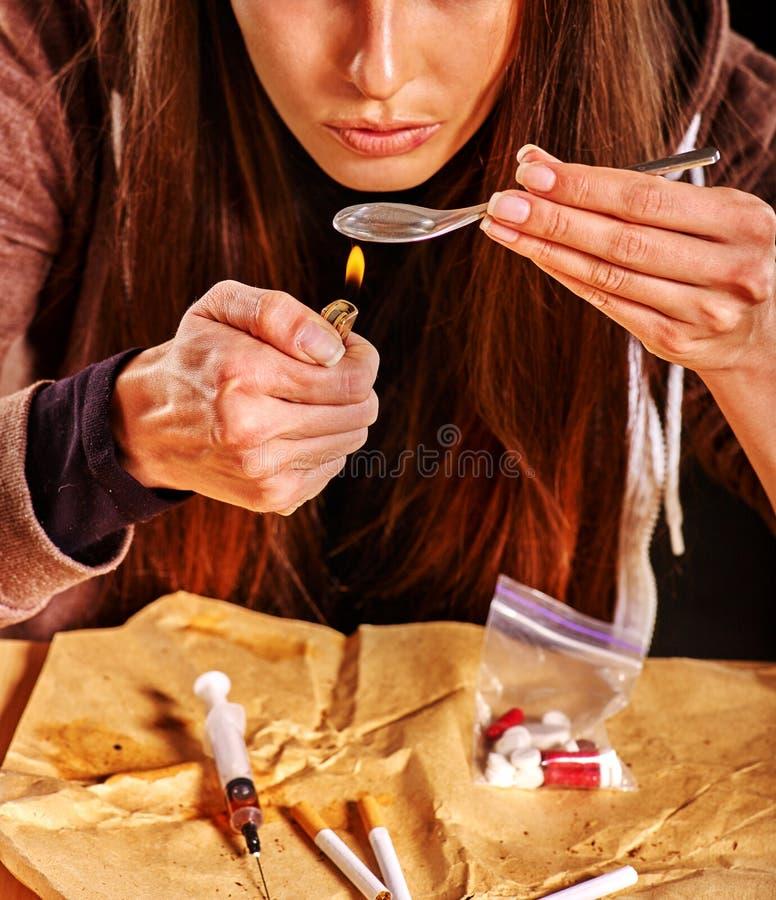 Intoxiqué de fille avec la cuillère et l'allumeur d'héroïne photos stock
